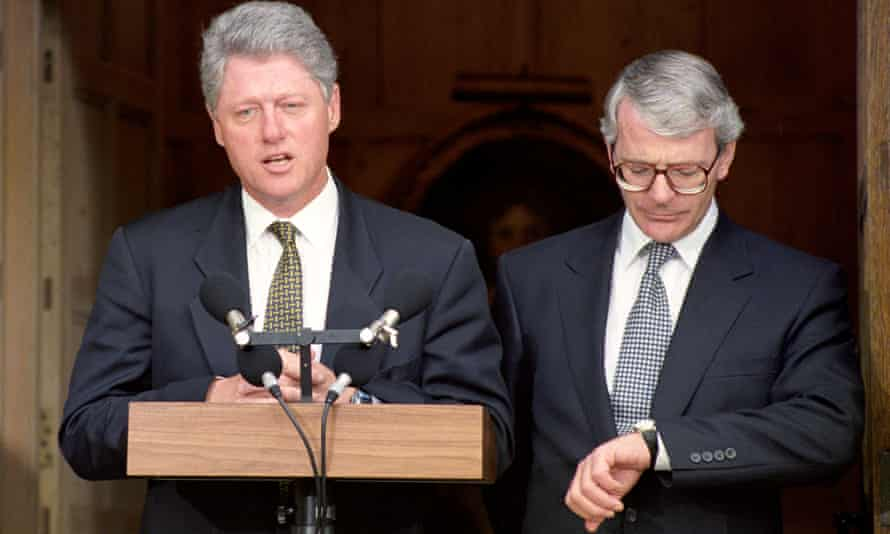 John Major checks his watch as Bill Clinton addresses the media at Chequers in 1994