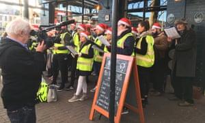 Jim Sheridan films Ian Bailey with Christmas carol singers in Dublin