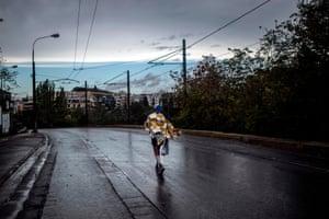 A runner walks outside the Panathenaic stadium after finishing the 37th Athens Marathon