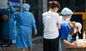 People write down their personal information before they are tested for coronavirus (Covid-19) at a temporary coronavirus testing stationin Seoul