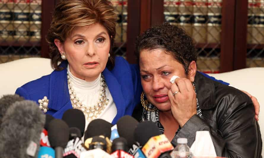 Gloria Allred speaking at a press conference with her arm around on of the alleged victims of Bill Cosby