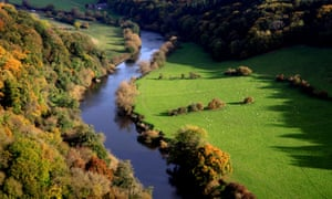 A meandering river bordered by woods in autumn colours and green fields