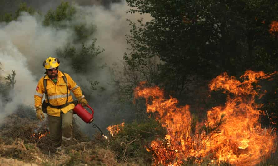 A firefighter lights a controlled fire to bring wildfires under control