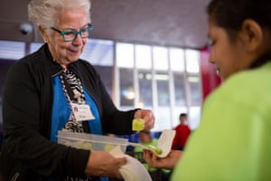 Eva Elisa, a volunteer from San Antonio's Interfaith Welcome Coalition, greets migrants at a bus station.