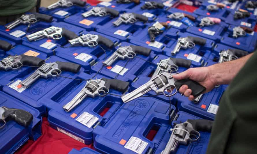 People look at handguns as thousands of customers and hundreds of dealers sell, show, and buy guns and other items during The Nation's Gun Show in Chantilly, Virginia, earlier this month.