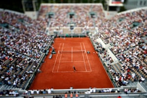 In a photograph created with a tilt-shift lens, Belgium's David Goffin serves to Marco Cecchinato of Italy during their fourth round match at the French Open.