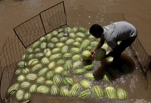 A street vendor In Jammu cools melons in a canal