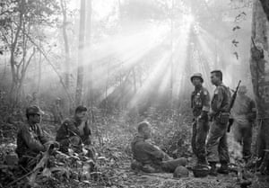 Sunlight breaks through dense foliage around the town of Binh Gia as South Vietnamese troops, joined by U.S. advisers, rest after a cold, damp, and tense night of waiting in an ambush position for a Viet Cong attack that did not come, January 1965