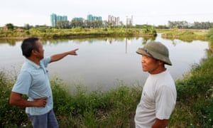 Dang Van Dat points to an Ecopark construction site as he stands with veteran Le Dung on an area involved in April 24's land seizure in Van Giang district<br>Dang Van Dat.