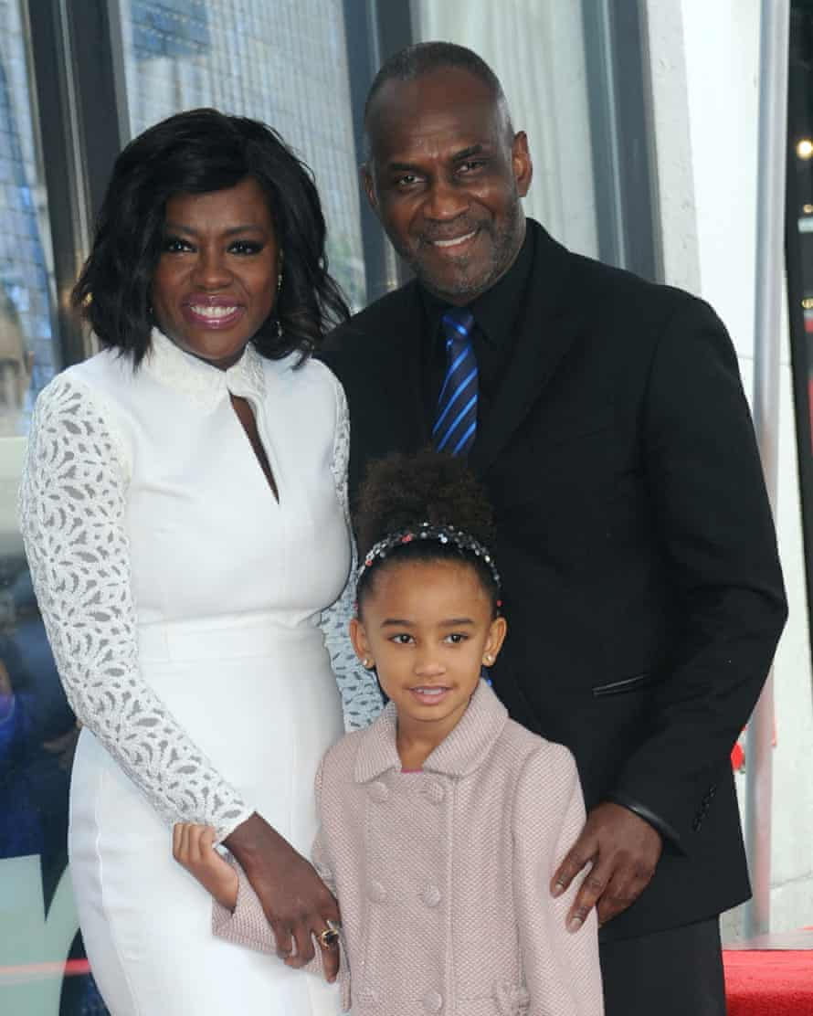 With her husband, actor Julius Tennon, and daughter.