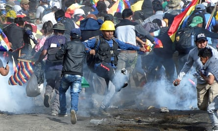 Coca growers and supporters of former President Morales run away from tear gas during clashes with riot police in Sacaba, in the outskirts of Cochabamba.