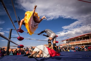 Silvina La Poderosa jumps from a corner of the ring to land on her opponent, Reyna Torres, during a promotional wrestling match fight in Senkata, El Alto