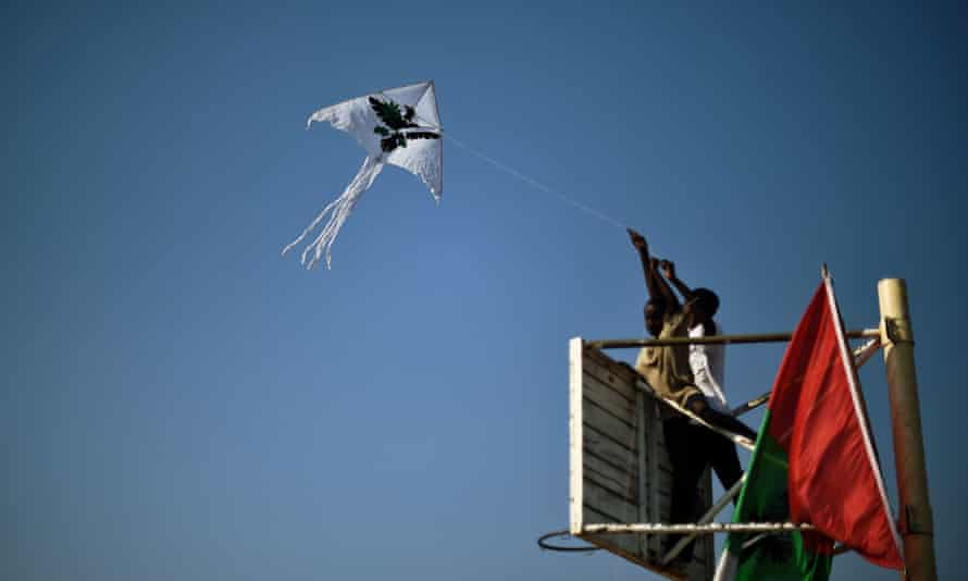 Boys fly a kite bearing the symbol of Burundi's ruling CNDD-FDD party during a rally last week.