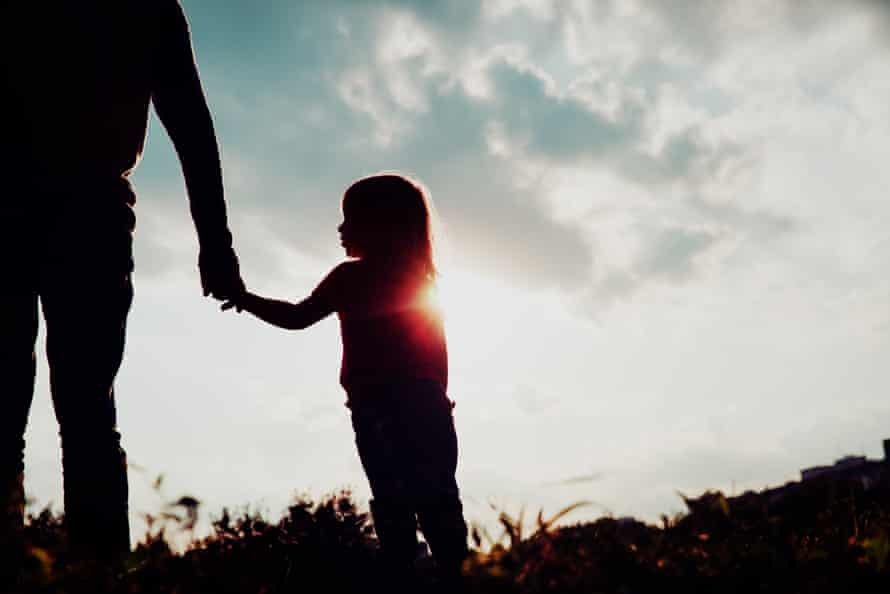 silhouette of little girl holding parent hand at sunset sky