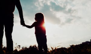 A silhouette of a young girl holding an adult's hand
