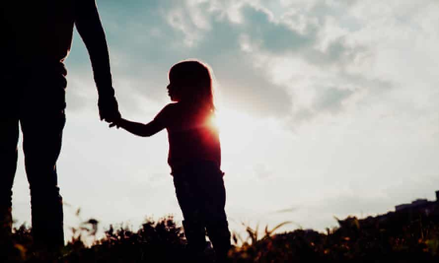 Silhouette of girl holding a parent's hand.