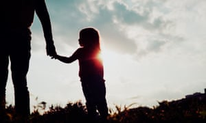 Silhouette of little girl holding adult's hand at sunset