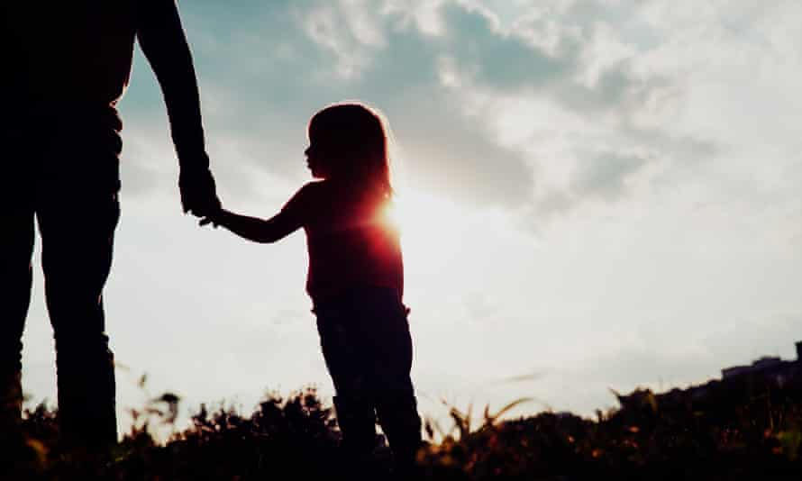 Silhouette of a little girl holding her father's hand at sunset