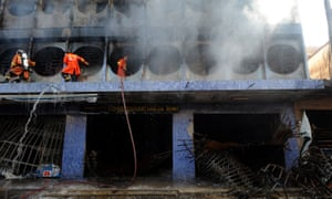Thai firefighters spray water on burning buildings