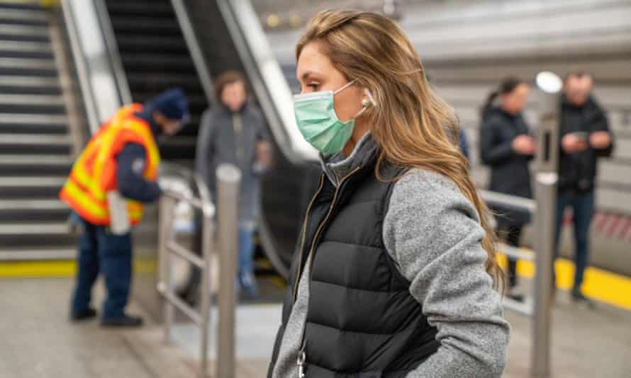 A commuter wearing a protective mask walks through the 86th subway station in New York.
