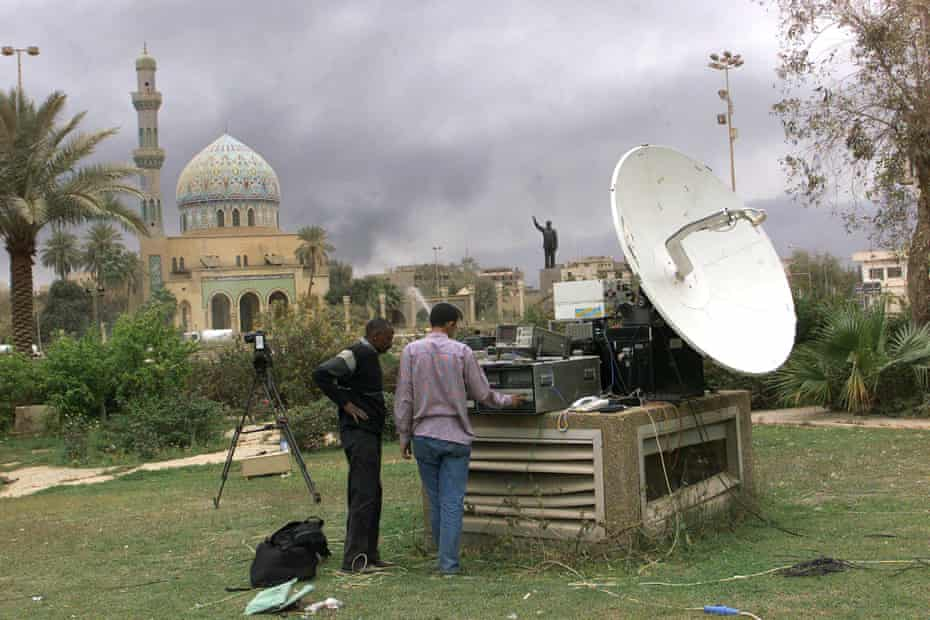 Journalists in the garden of Palestine Hotel in Baghdad on 30 March 2003, with a view of the soon-to-be-toppled statue.