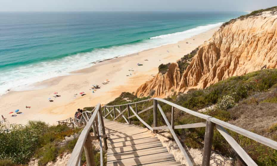 Wooden staircase in the sandstone cliffs giving access to Gale beach, Comporta, Portugal