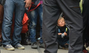 A boy waits for his parents to be registered after police stopped their train in German town of Freilassing