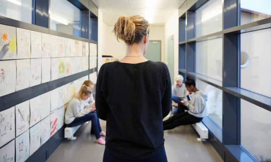 Teacher and pupils in a school corridor