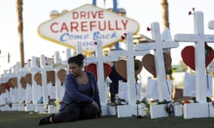 Cece Navarrette sits near a cross for her cousin, Bailey Schweitzer, who was among those killed on Friday, 6 October, 2017 when a gunman opened fire on an outdoor music concert in Las Vegas.