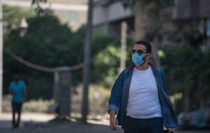 A man wearing a face mask walks on a street in Giza.