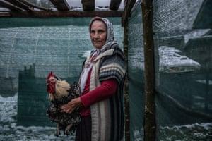 Nazira, a survivor of Srebrenica, in a henhouse behind her apartment at Jezevac refugee camp