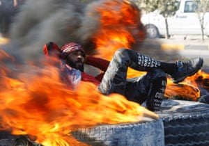 Najaf, Iraq: an Iraqi demonstrator is surrounded by burning tires as he blocks a road during ongoing anti-government protests