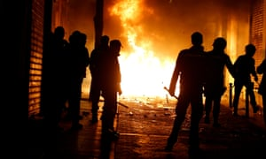Spanish police officers stand in front of burning rubbish bins during clashes in Madrid on Thursday night.
