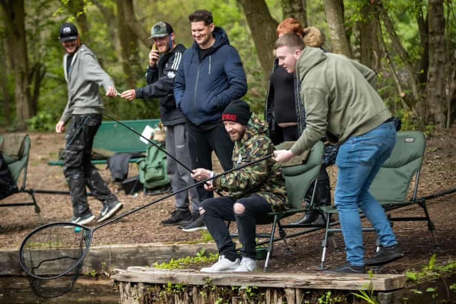 James Murphy (sitting) catches a fish at Boggart Hall Clough.