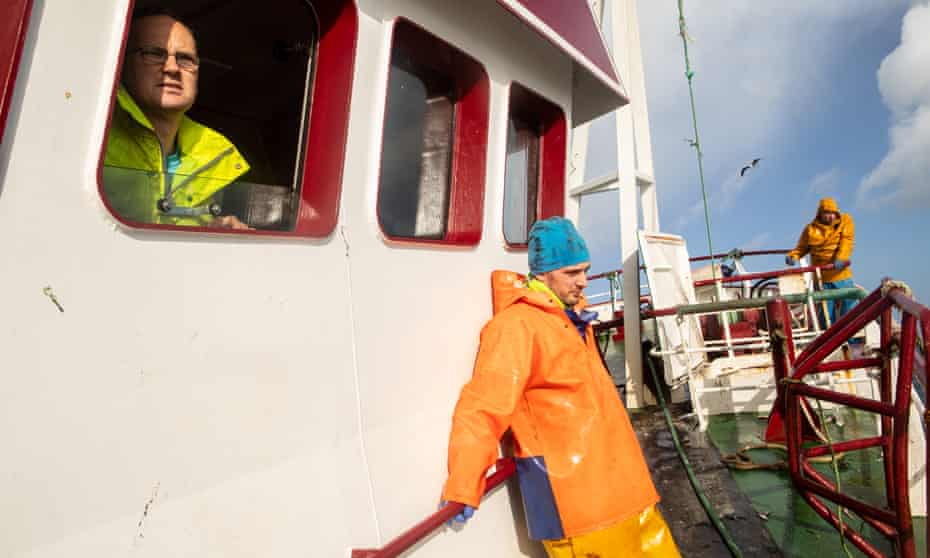 Skipper David Stevens looks out from the wheelhouse as the crew prepares for the nets to be pulled in.