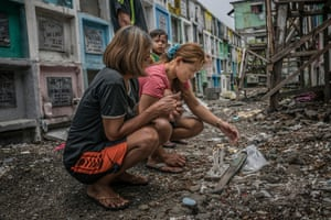 Appolinaria Salita, 58, Mary Grace's mother is to camera left, and youngest son, Noel, 3 years old, looks on from behind with his father, Cerlon, 27. Navotas Catholic Cemetery, Metro Manila, Philippines