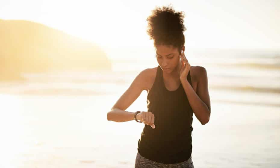 Sporty woman checking a device while working out at the beach