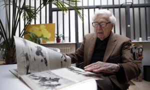 John Morris looking at Robert Capa pictures from D-day during an interview in Paris in 2014.
