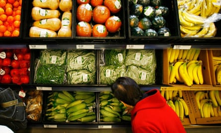 A shopper selects from pre-packaged produce
