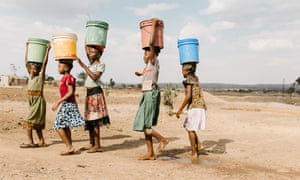 Girls carry water away from a privately owned shallow well on the edge of Nyarugusu. This is the closest water source to Nyarugusu Dispensary, a 15-minute drive away; the well runs low in the dry season and is subject to contamination in the rainy season.
