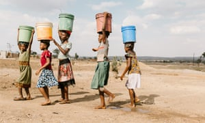 Girls carry water away from a privately owned shallow well on the edge of Nyarugusu, in Tanzania's Geita district