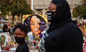 A mother and son attend a demonstration in downtown Louisville, close to the makeshift memorial for Breonna Taylor.
