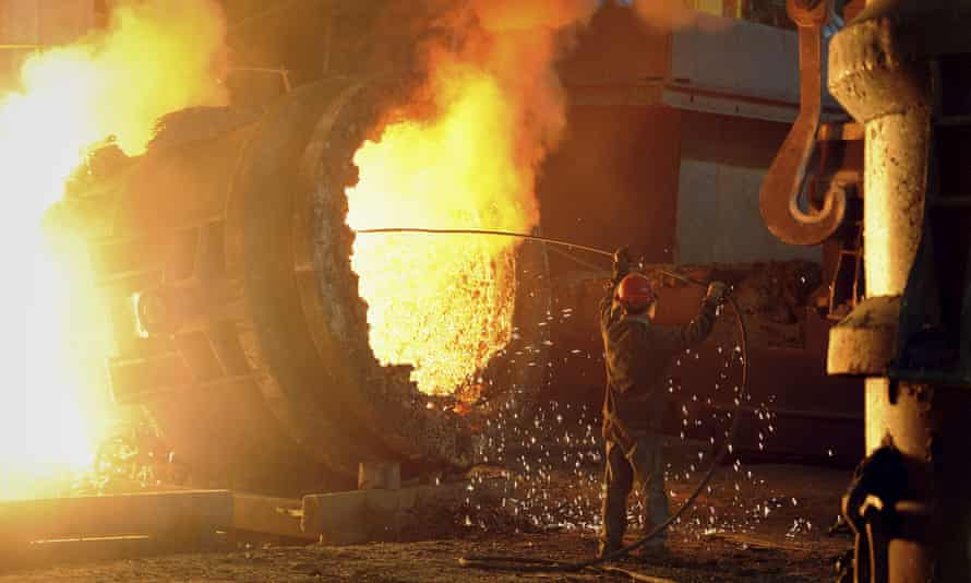 A steel worker operates a furnace at a steel manufacturing plant in Hefei, Anhui province