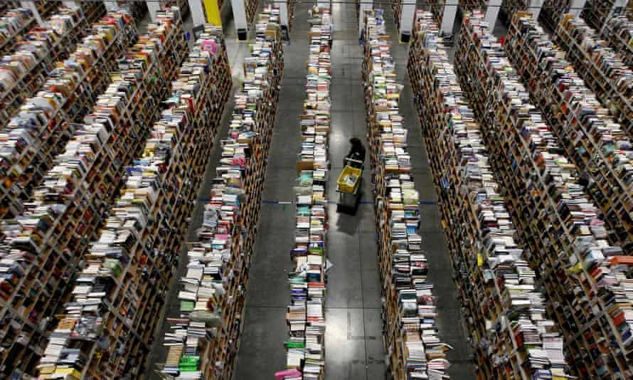 A worker gathers items for delivery from the warehouse floor at an Amazon distribution center in Phoenix.