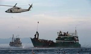 罗兴亚移民游泳收集泰国军用直升机降落的食物供应