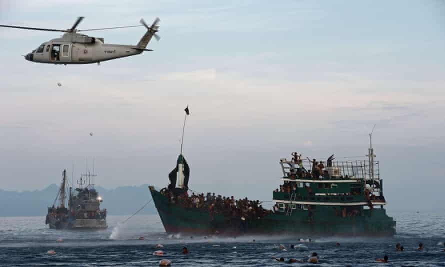 Rohingya migrants swimming to collect food supplies dropped by a Thai army helicopter