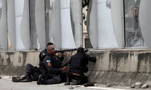 Policemen take up positions during an operation against drug dealers near the Maré slum complex in Rio de Janeiro on Tuesday.