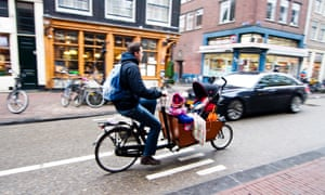 Riding a bakfiets with child carrier in Amsterdam. Father transports his children in a box bike around the Netherlands' capital.