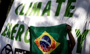 A protester holds a Brazilian flag depicting the country's emblem in flames in front of the Brazilian Embassy during a demonstration organised by Extinction Rebellion activists in Brussels, 26 August 2019.