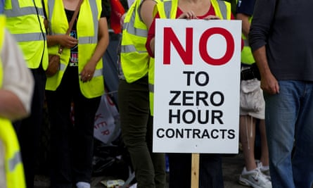 A protest in Wigan, with one demonstrator hiolding a,loft a placard declaring 'No to zero-hours contracts.'